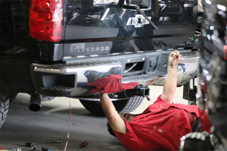 Employee at North Texas Collision Center providing repairs on a vehicle after an accident